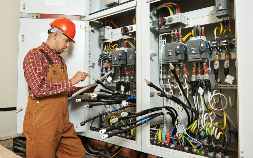 Electrician in front of switchboard holding specification