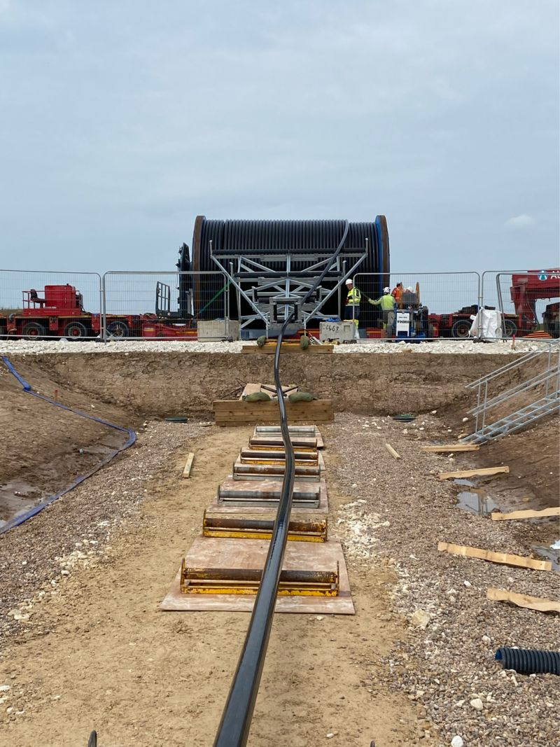 Image Courtesy | Max States Site Engineer at Balfour Beatty plc (Viking Link) – here the EHV 526kV cable is pictured being pulled from a 62 tonne cable drum (1240m circuit) into the cable trench via rollers in July 2021. Viking Link is a 1,400 MW HVDC submarine power cable under construction between the United Kingdom and Denmark.